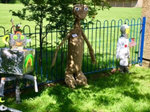 Photograph of scarecrows on the railings outside the village hall